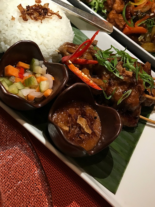 Chicken satay with peanut sauce with a side of steamed sticky rice